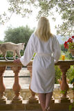 Cat next to woman in bathrobe on patio Stock Photo