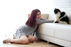 Cat owner at home. Attractive smiling Hispanic woman playing with black and white cat at home royalty free stock photos