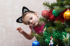 Cat painted little girl peeking out from behind Christmas tree Royalty Free Stock Image