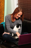 Cat and pretty woman looking at computer Stock Photo