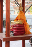 A cat is resting in front of a statue of Buddha in the courtyard of a temple (Thailand) Royalty Free Stock Photos