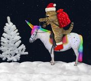 Cat rides the unicorn in the forest. The cat in the Santa Claus outfit is riding the real unicorn in the winter forest at night royalty free stock photos