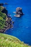 Cat Rock, Rebun Island, Japan. Nekoiwa, or `Cat Rock,` juts out of the sea along the green coast of Rebun Island, Japan; a fishing boat rests in the clear blue Stock Image