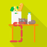Cat. With sausage on the kitchen table Stock Photos