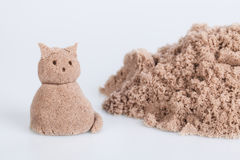 Cat sculpture from wet sand on a white background. Closeup of cat sculpture from wet sand on a white background Royalty Free Stock Photo