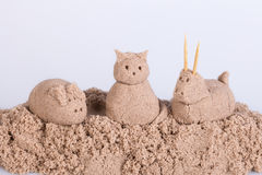 Cat sculpture from wet sand on a white background. Cat, pig and sheep sculptures from wet sand on a white background Royalty Free Stock Photos