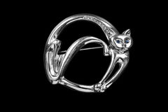 Cat shaped brooch. Silver brooch in the shape of a cat isolated over black Royalty Free Stock Photo