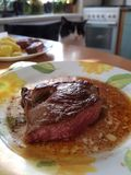 Cat at the table. Cat sitting at dinner table, steak on a plate and cat in the background royalty free stock images