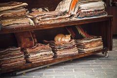 Cat sitting on stacked colorful fabrics, Istanbul, Turkey. Royalty Free Stock Photos