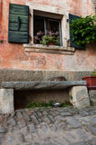 Cat sleeping on a bench in front of an old house. In Istria, Groznjan, Croatia Royalty Free Stock Photos