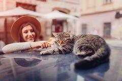 Cat sleeping on car roof on city street. Young wooman awaking cat. Girl strokes pet. Cat sleeping on car roof on city street. Young smiling wooman awaking cat stock image