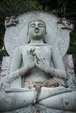 Cat sleeping on lap Buddha statues. Royalty Free Stock Photo
