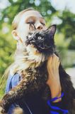 Cat tortoiseshell Maine Coon in the hands of the girl. A girl walks with a cat along the street royalty free stock images
