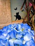 Cat wall art with butterflies and blue flowers. Small black cat wall art with butterflies and blue flowers hidden away stock photos