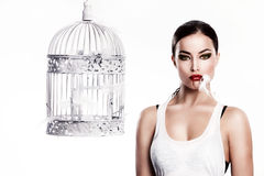 Cat woman ate a bird. Cat woman with feathers in mouth stand beside empty cage Royalty Free Stock Image