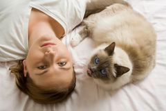 Cat and woman looking up. From a white bed Royalty Free Stock Photo