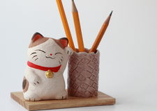 Cat on a wooden stand under pencils. On a white background stock photo
