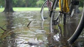 Cataclismo da inundação em Tailândia Bicicletas que estão na poça das águas profundas Estação da chuva pesada após o clima que mu