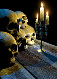 Catacombs. Row of skulls on vintage wooden table, enlighted by a candlestick stock illustration
