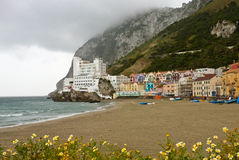 Catalan Bay and Beach, Gibraltar. View of Catalan Bay and beach in Gibraltar on a cloudy and rainy afternoon with colourful apartments and boats in the old Royalty Free Stock Photos