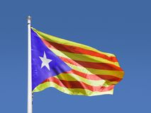 Catalan estelada flag with blue sky. Catalan estelada flag separatist independence flag waves in blue sky Stock Photo