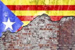 Catalan Flag On Grungy Wall. Grungy old brick wall with Catalan flag on broken render surface Royalty Free Stock Photo
