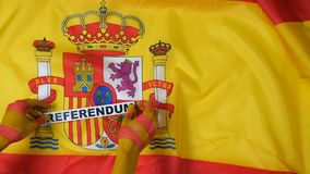 Catalan hands put the card - referendum on the flag of Spain stock video