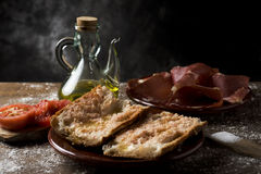 Catalan pa amb tomaquet with serrano ham. Closeup of a plate with typical catalan pa amb tomaquet, bread with tomato dressed with olive oil, a plate with some Stock Photos