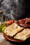 Catalan pa amb tomaquet with serrano ham. Closeup of a plate with typical catalan pa amb tomaquet, bread with tomato dressed with olive oil, a plate with some Royalty Free Stock Photography