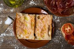Catalan pa amb tomaquet and serrano ham. High-angle shot of typical catalan pa amb tomaquet, bread with tomato, placed on a plate, on a rustic wooden table next Royalty Free Stock Photos