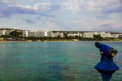 Catalejo en el terraplén del puerto para mirar la playa de la ciudad Imagenes de archivo