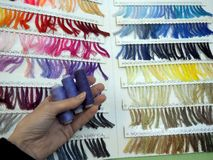 Catalog with samples of threads and three spools in hand royalty free stock image