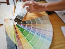 Catalogo di colore con la mano dell'uomo che seleziona per l'interior design fotografia stock