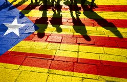 Catalonia flag with crowd of people. Group of people shadows, walking on sunny stone tiled street floor with painted Catalonia flag Stock Photography