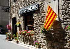 The Catalonian flag hangs outside a bakery on a pretty street in the pretty walled town of Villfranche de Conflent. In the south of France. This medieval city Royalty Free Stock Image