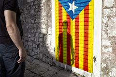 Catalonian flag with man. Man with shadow stands alone in old city and looking at painted Catalonian flag on the street wall Stock Images