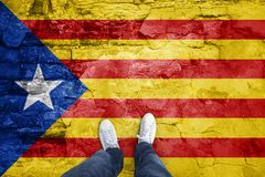Catalonian flag with a man. Point of view of a man standing on cracked cement floor with cracked Catalonian flag Stock Photography
