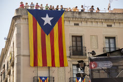 Catalonian Independence flag. Barcelona, Spain - September 20, 2015: A large Catalan flag , a symbol of Calalonian independence, hangs below onlookers watching Royalty Free Stock Photography