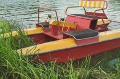 Catamarã de passeio do turista nos arbustos na costa Foto de Stock