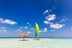 Catamarã na ilha tropical do banco de areia com para-sol, Maldivas Oceano Índico fotografia de stock