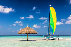Catamarã na ilha tropical do banco de areia com para-sol, Maldivas Oceano Índico imagens de stock royalty free