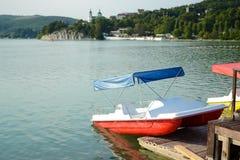 Catamaran aan de pijler op het blauwe meer in de bergen wordt vastgelegd die stock afbeelding
