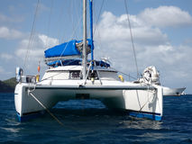 A catamaran at anchor in admiralty bay. A sailboat sheltered at a calm bay in the windward islands stock photography