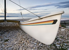 Catamaran in the Beach. Close up view of a catamaran on a rocky beach. White board with some stripes with the colors of rainbow. Photo taken at sunset Stock Image