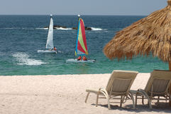 Catamaran Beach scene. Two catamaran sailboats near ocean shoreline with white recliners and grass palm umbrella in foreground stock photos