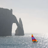 Catamaran and cliff. Colorful sailing catamaran in front of a huge misty cliff in France royalty free stock images