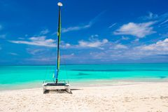 Catamaran with colorful sail on caribbean beach Stock Photo