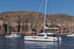 Catamaran dans la baie de santorini avec le drapeau de la Grèce Catamaran dans sant Photos stock