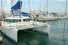 Catamaran and docked boats Stock Photography