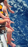 Catamaran Legs Over Water. Several sets of men's legs hanging off a catamaran over water Royalty Free Stock Photos